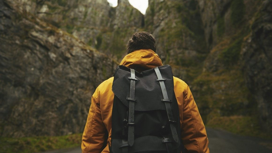 personne de dos qui porte une veste et un sac à dos